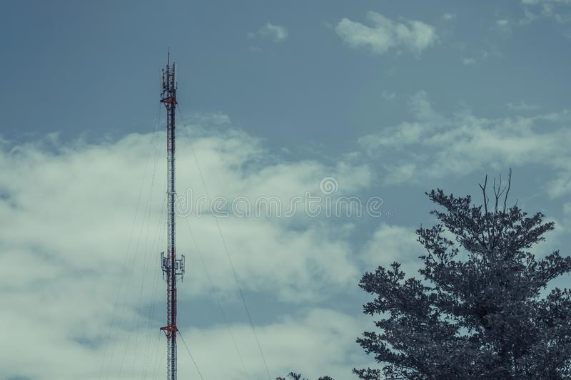 Mobile phone communication antenna tower with cloud on center bl royalty free stock photos