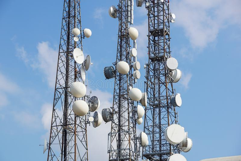 Mobile phone communication antenna tower with satellite dish on blue sky background, Telecommunication tower stock photography