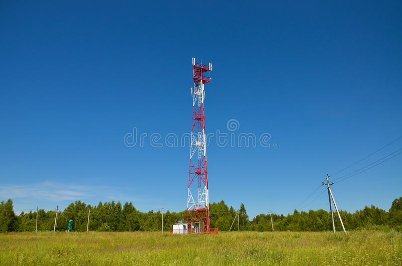 Mobile phone communication radio tv tower, mast, cell microwave antennas and transmitter against the blue sky and trees stock photography