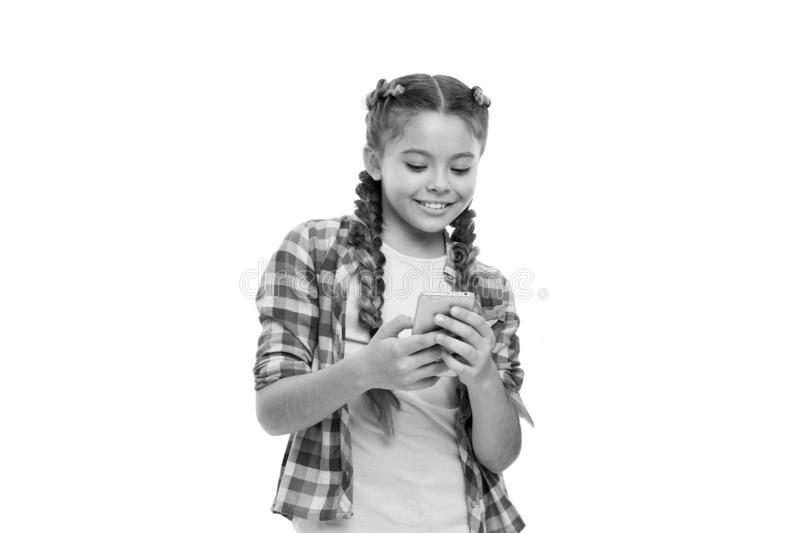 Mobile phone dependence. Girl cute small child smiling to phone screen. She likes internet surfing and social networks. Problem of young generation. Mobile royalty free stock photo