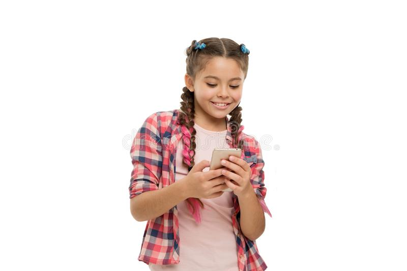 Mobile phone dependence. Girl cute small child smiling to phone screen. She likes internet surfing and social networks stock photos