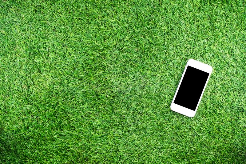 Mobile phone with earphone and sport equipment on grass background., top view. royalty free stock image