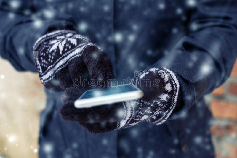 Mobile phone and female hands with winter gloves stock photos