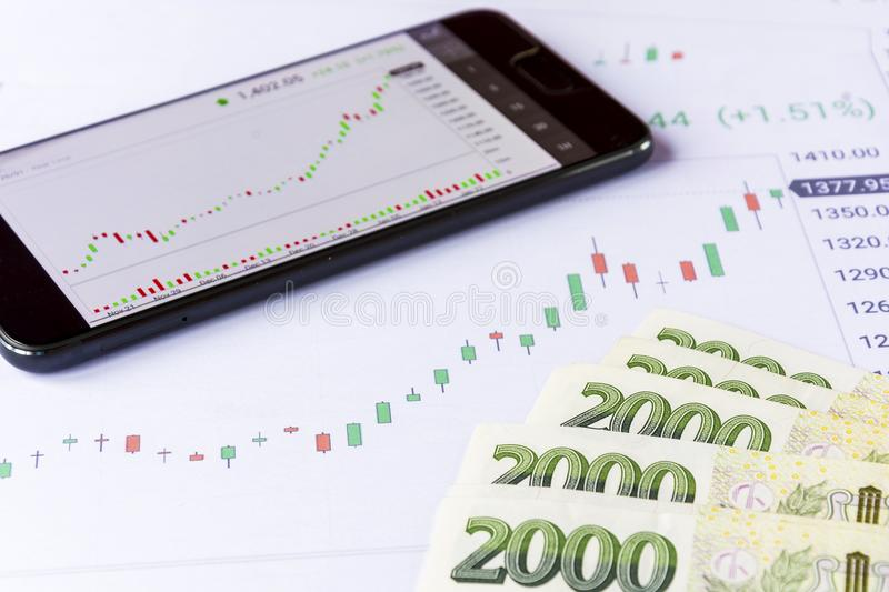 Mobile phone with green czech money on economic charts stock photos