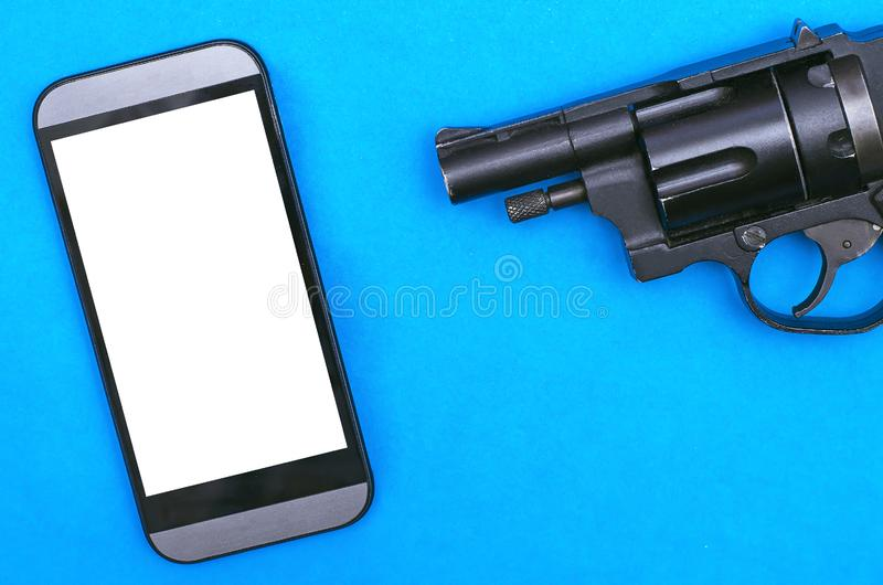Mobile phone and gun. Mobile phone with a blank screen and black handgun on a blue background, smash, smashing, brake, kill, pistol, revolver, weapon, shoot stock images