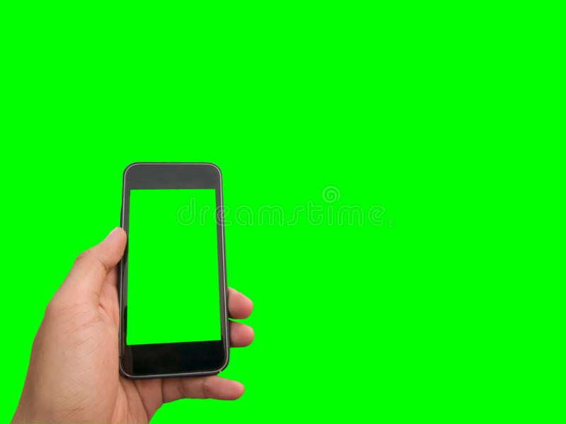 Mobile phone in hand. With blank screen isolated on green background stock images