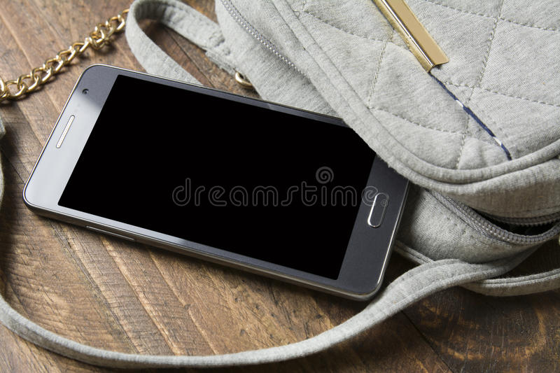 Mobile phone and handbag Women stock photography