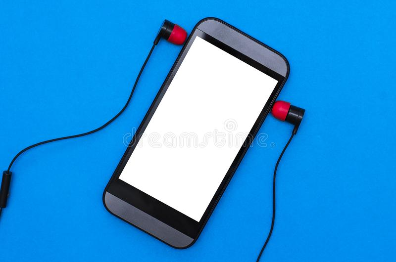 Mobile phone and headphones. Mobile phone with blank screen and headphones isolated on a blue background, music, earphones, empty, template, mock, up, mockup stock photos