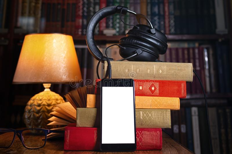 Mobile phone, headphones and a stack of books near the lamp. Concept of training and audiobooks. Library bookcase in the royalty free stock photo