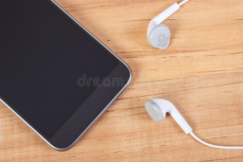 Mobile phone with headphones, using electronics equipment stock image