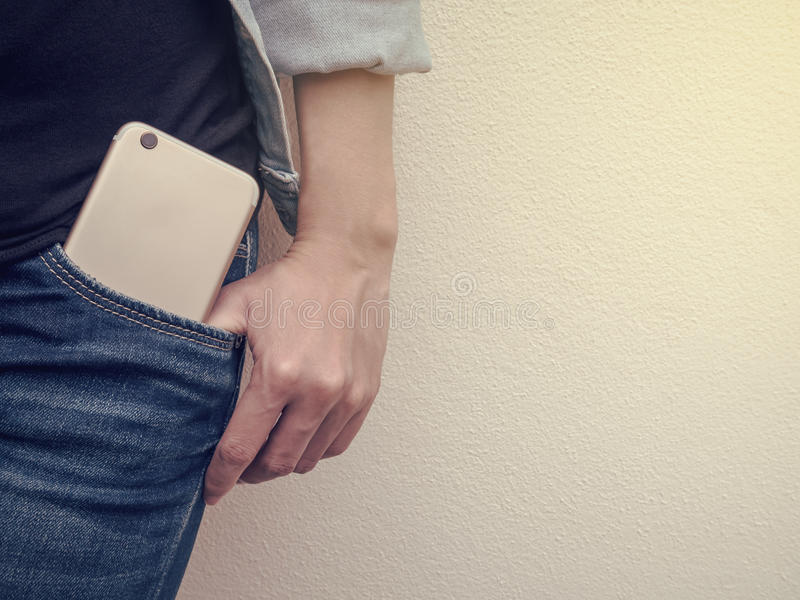 Mobile phone in jeans pocket royalty free stock photos