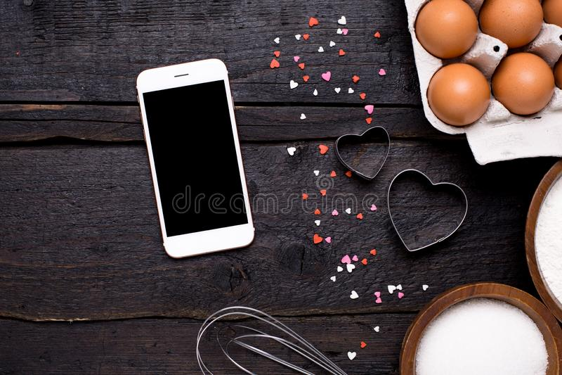 Mobile phone , kitchen tools and hearts on a wooden background stock image