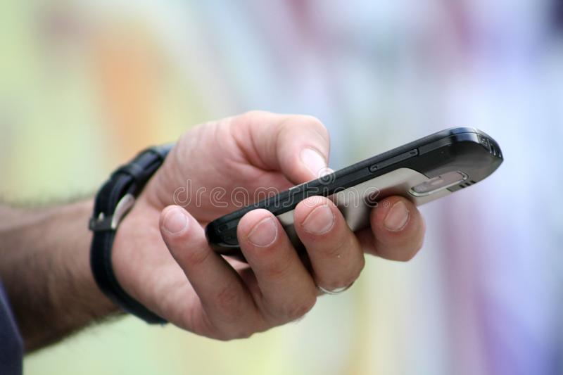 Mobile phone in mans hand royalty free stock image
