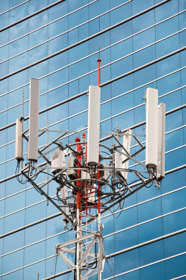 Mobile phone mast antenna. With office building background stock images