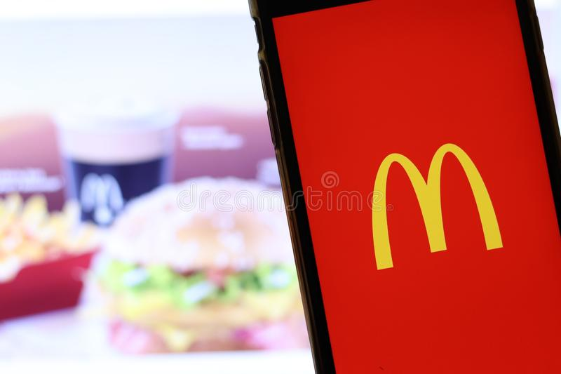 Mobile phone with McDonald`s logo on screen close up with website on laptop. Blurred background with McDonalds food stock photo