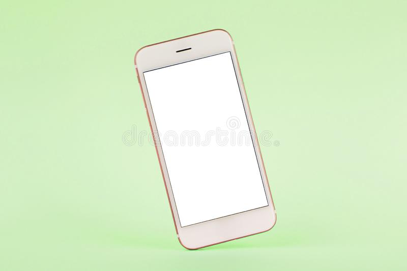 Mobile phone mock up on green pastel background, technology and busiess concept. Side view royalty free stock photos