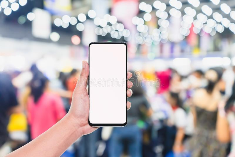 Mobile phone mockup image, hand holding blank screen mobile smart phone with blurred  Crowd of people in the shopping store, royalty free stock photos