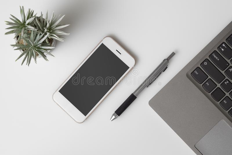 Mobile phone mockup, top view of White office desk table with mockup blank screen smartphone and computer laptop. Flat lay top royalty free stock images