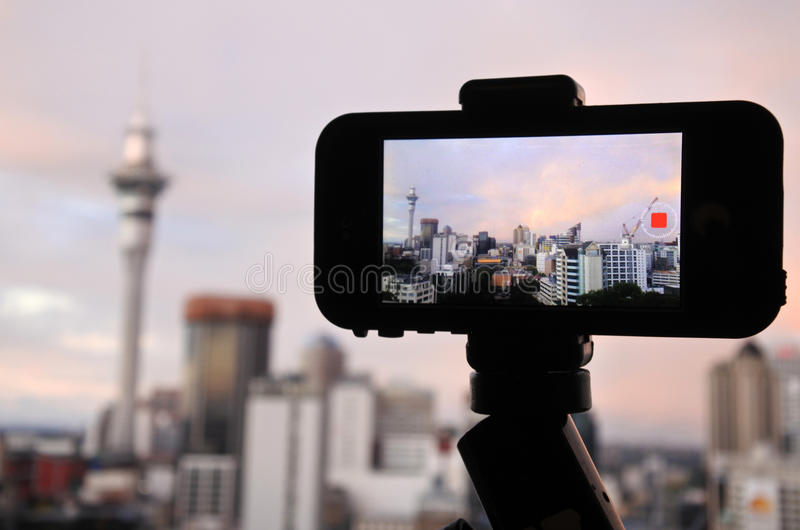 Mobile phone photographing and filming a rainbow in a rain cloud. Over Auckland skyline, New Zealand royalty free stock image