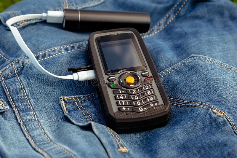 A mobile phone and a power bank on a jeans background in nature. stock images