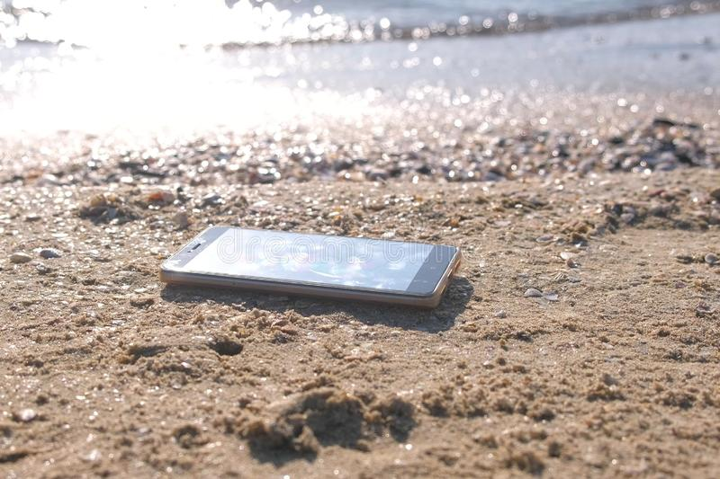 Mobile phone on the sandy sea beach with waves. royalty free stock image