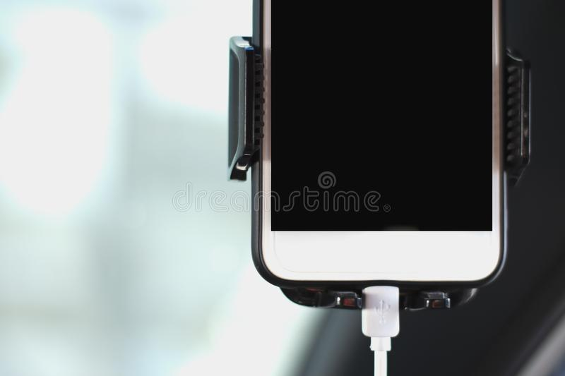 Mobile phone with screen attached to the windshield holder. For navigation, travel and safety stock photos