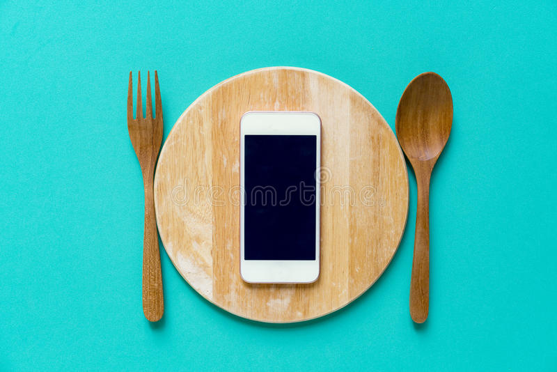 Mobile phone served on wood plate. Concept and idea stock image