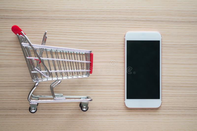 Mobile phone with shopping cart on wood table background shopping online concept royalty free stock image