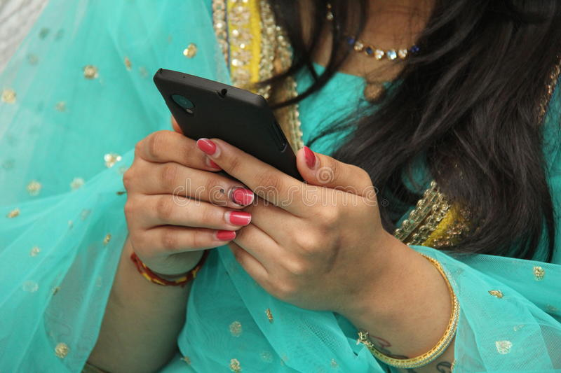 Mobile phone in Teenager girl's hand. Indian teenager girl having nail polish using mobile phone stock photos