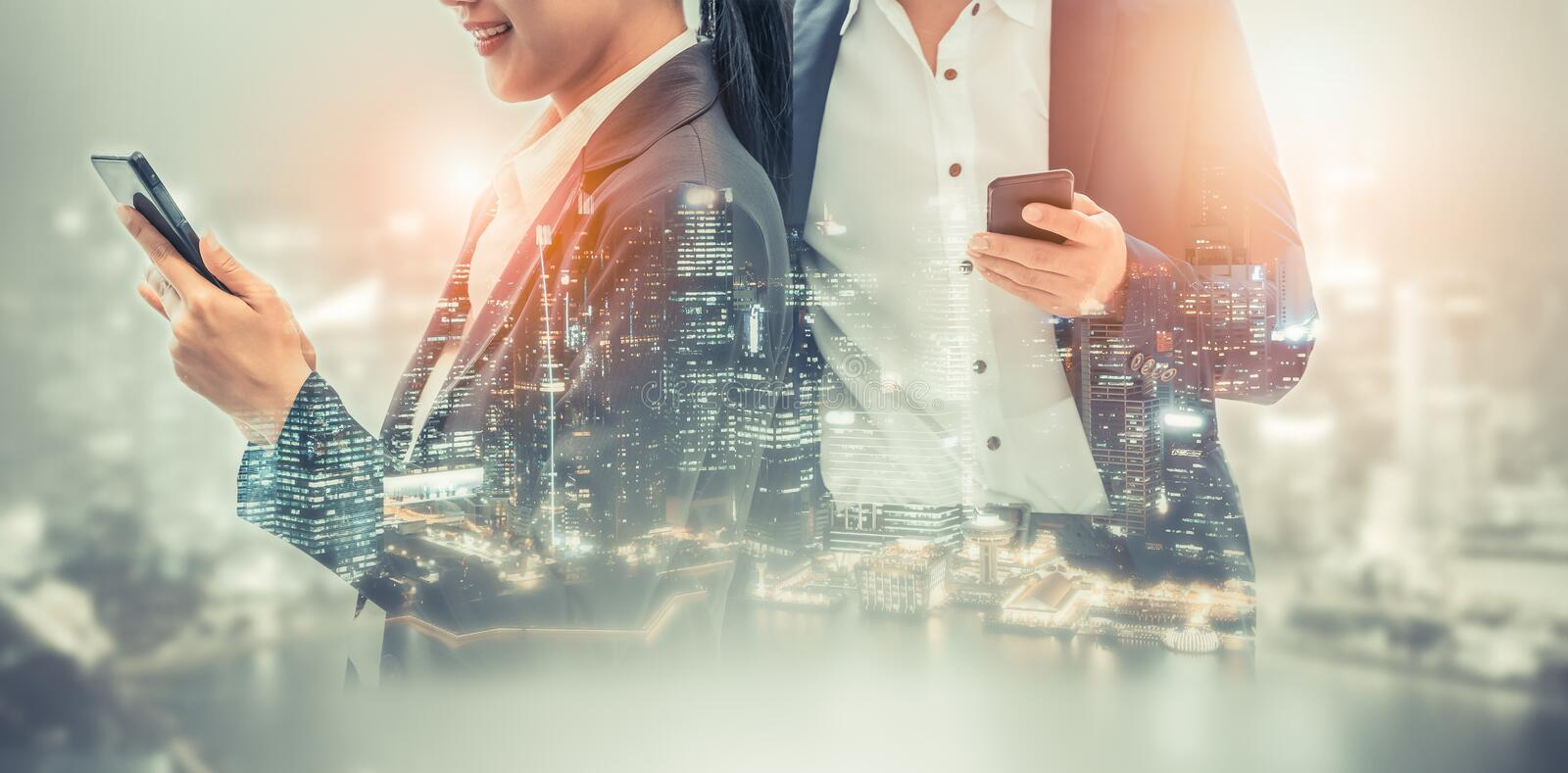 Mobile phone telecommunication technology concept. Young business people using mobile phone with modern city buildings background. Future telecommunication stock photo