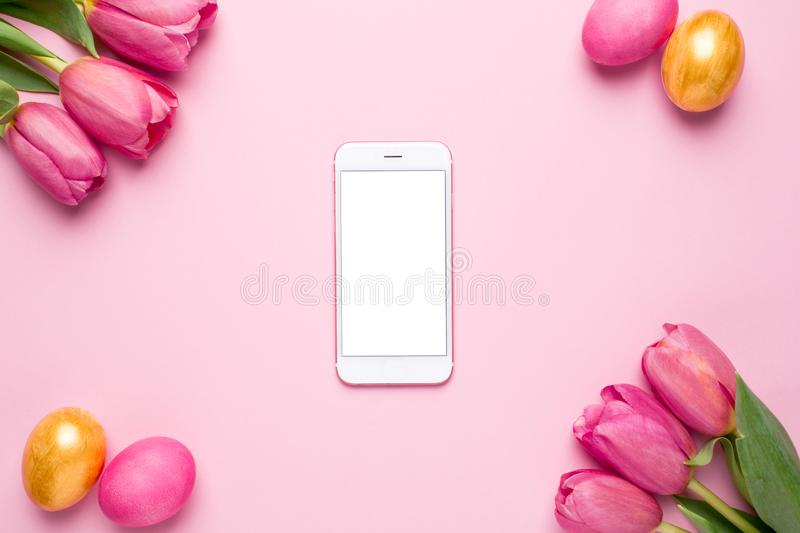 Mobile phone with white screen, easter eggs and flowers tulips on pink background. Top view stock images