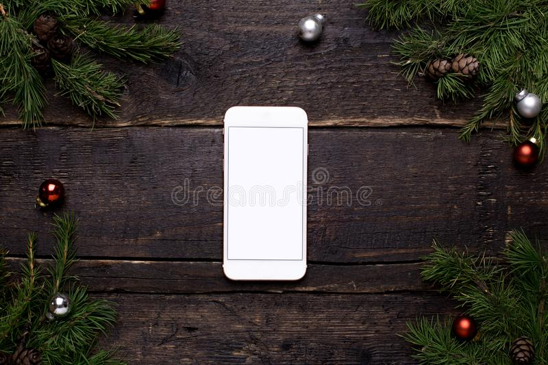 Mobile phone on a wooden table with a Christmas tree and chrismas decoration stock photography