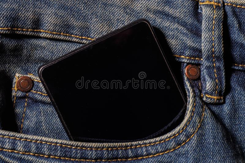 Mobile phone in your pocket jeans. Close-up Photos stock photos