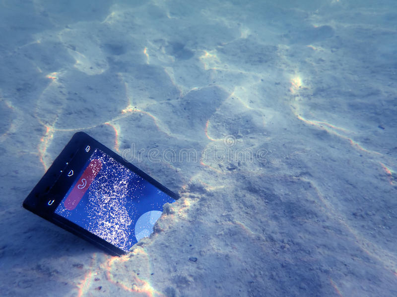 Mobile phones on the sand under the sea water. stock image