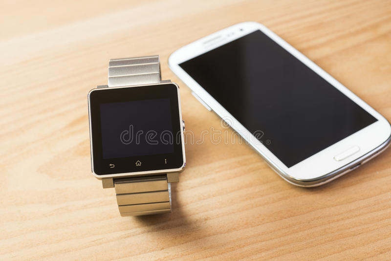 Mobile phones, smart watches and laptop computers. Business personnel essential items, mobile phones, smart watches and laptop computers stock images