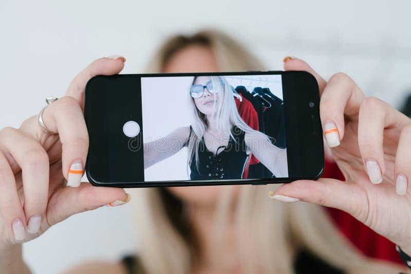 Mobile photography selfie girl blogger lifestyle. Mobile photography and selfie trend. young stylish girl taking photoof herself using smartphone. social media stock photo