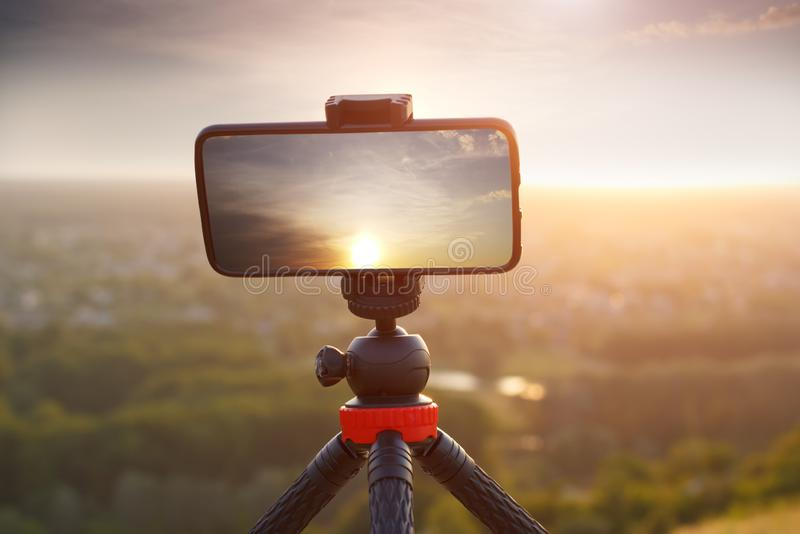 Mobile photography with smartphone on tripod shooting landscape with sunset royalty free stock images