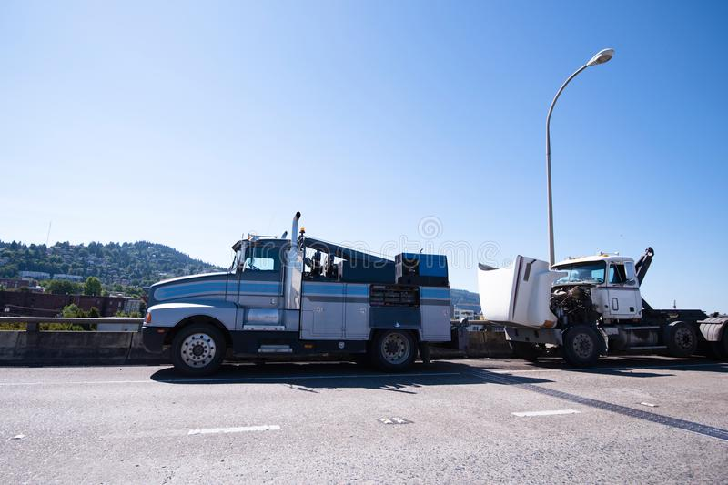 Mobile repair shop on the basis of towing semi truck is repairing faulty semi truck on the road stock photography