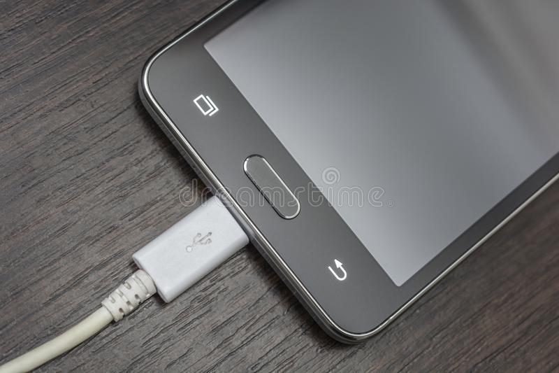 Mobile smart phones charging on wooden desk stock images