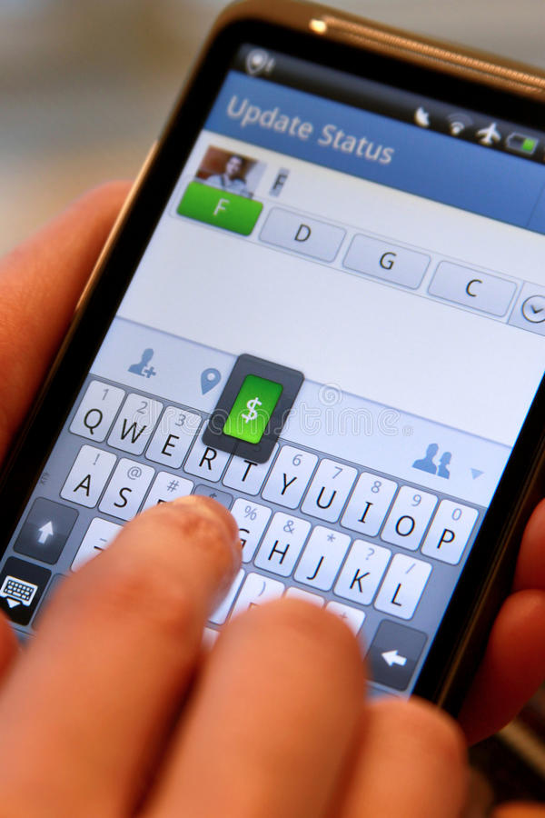Mobile and social networking. A mobile user updating status on a social networking mobile site for Facebook on an Android based mobile smartphone royalty free stock photo