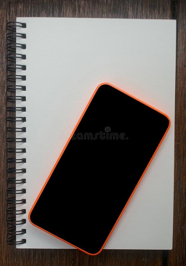Mobile, téléphone portable placé sur le nootebook ouvert sur la table en bois photos stock