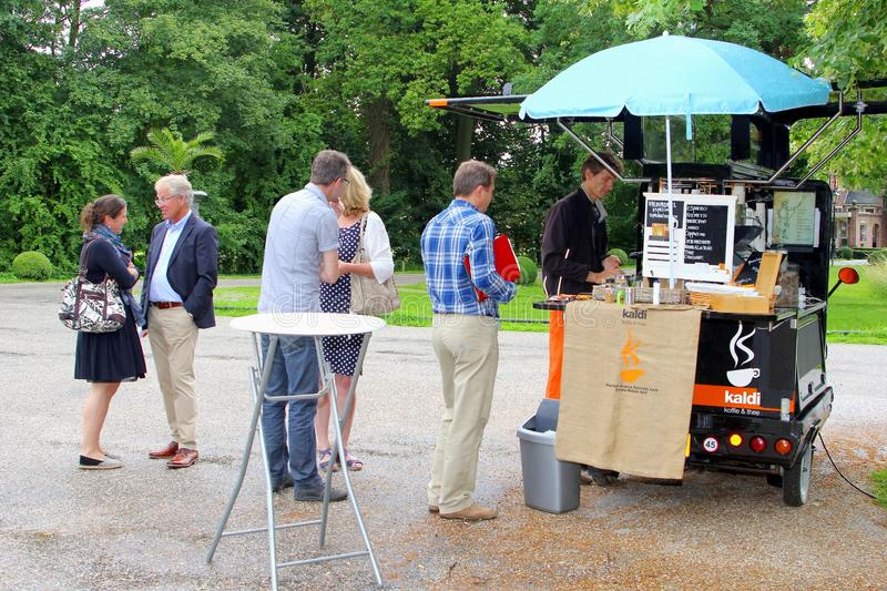 Mobile take away coffee franchise business, Netherlands. Man is selling take away cappucino, espresso coffee and tea in a mobile coffee shop on wheels in a small royalty free stock photography