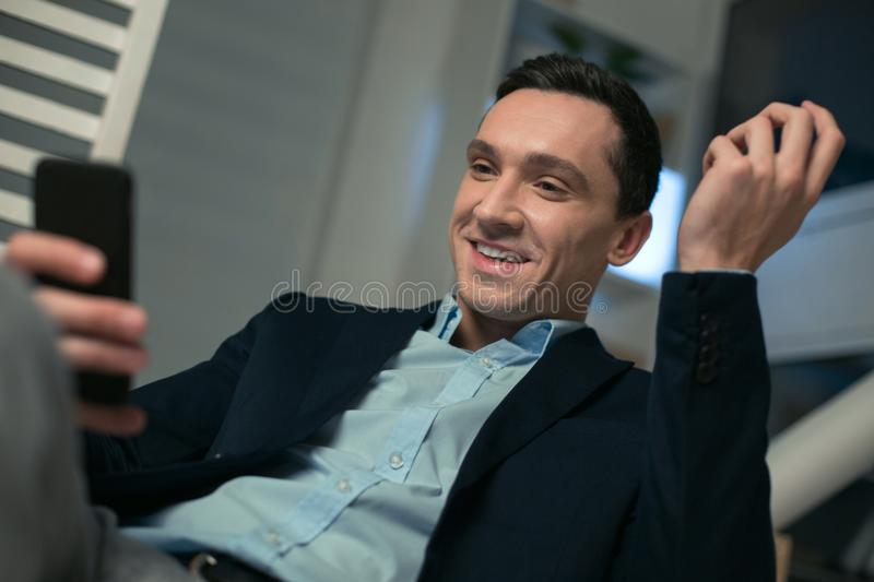 Positive real estate agent texting message. Mobile technology. Handsome pleasant real estate agent sitting while laughing and using phone royalty free stock photos