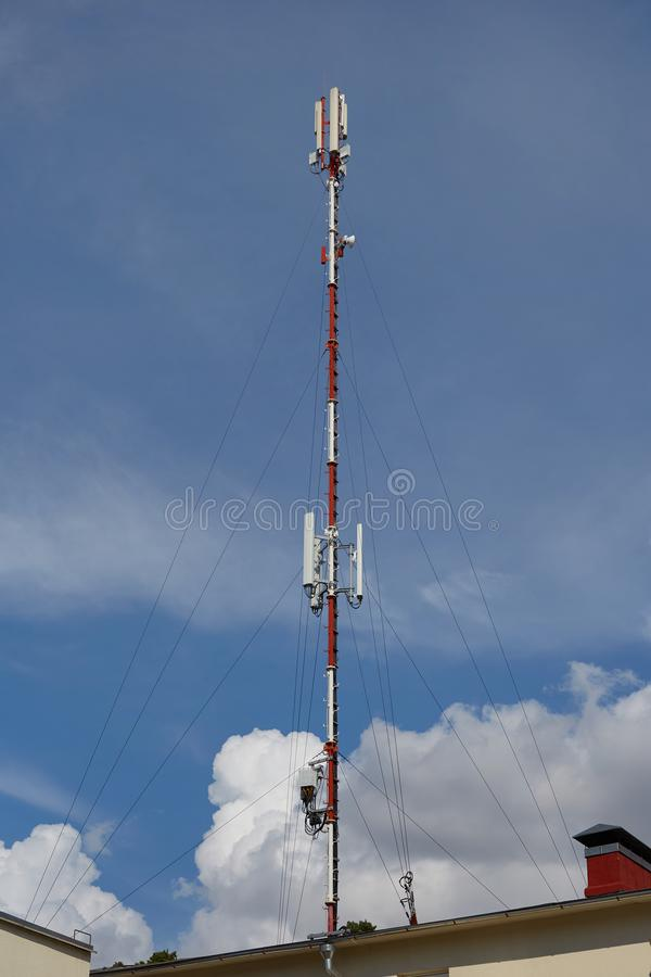 Mobile telephone radio network antenna on the building roof broadcasting signal over the city. Day royalty free stock photo