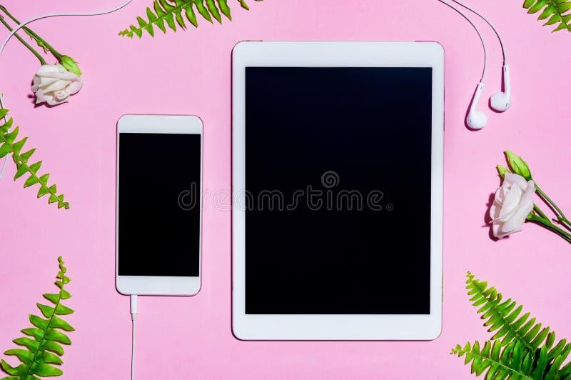 Mobile und digitale Tablette auf Rosa stockfotos