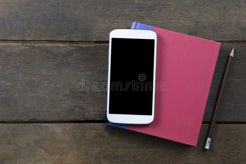 Mobile vide d'écran sur le livre et le crayon rouges de couverture sur vieux b en bois images stock