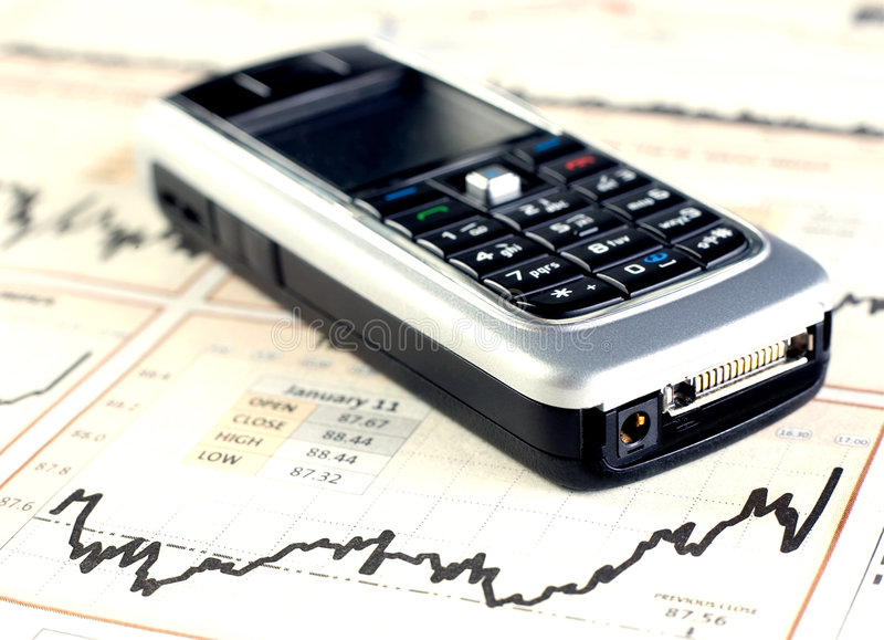 Mobilephone on stock chart. Mobile phone on stock chart - yellow tint royalty free stock photo