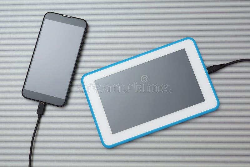 Mobiler intelligenter Telefon- und Tabletten-PC, der auf silbernem Schreibtisch auflädt lizenzfreie stockfotos