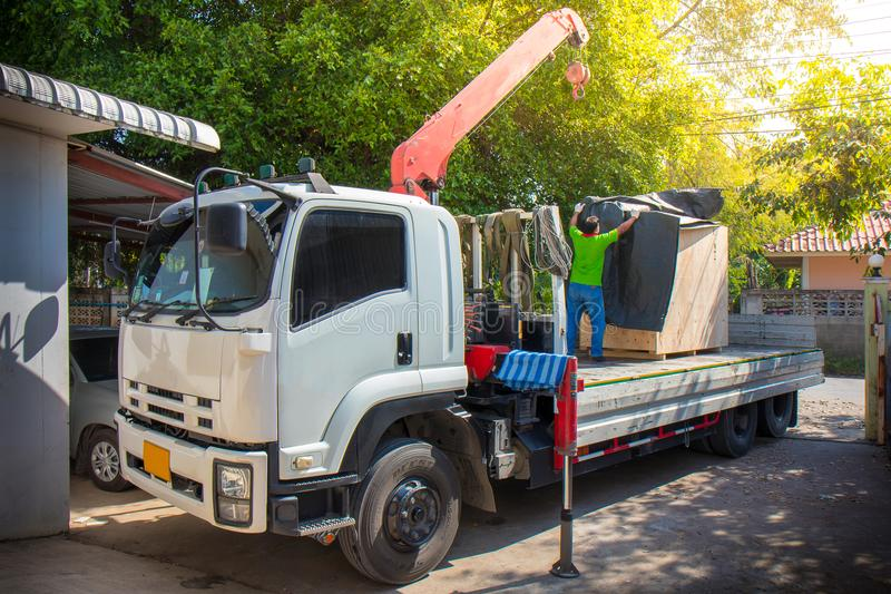Mobiler Kran entlädt, Masche vom LKW-Anhänger verstärkend stockbild