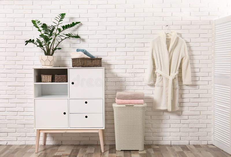 Mobilia con gli asciugamani puliti e l'abito vicino al muro di mattoni immagini stock libere da diritti